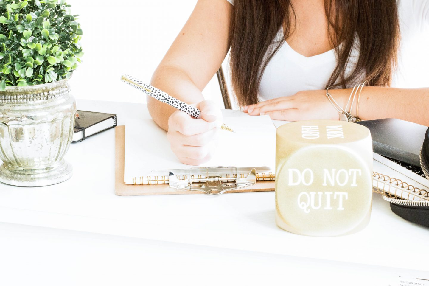 Do not quit desktop ornament. Gold tones. Woman writing. Stay focused on your goals.
