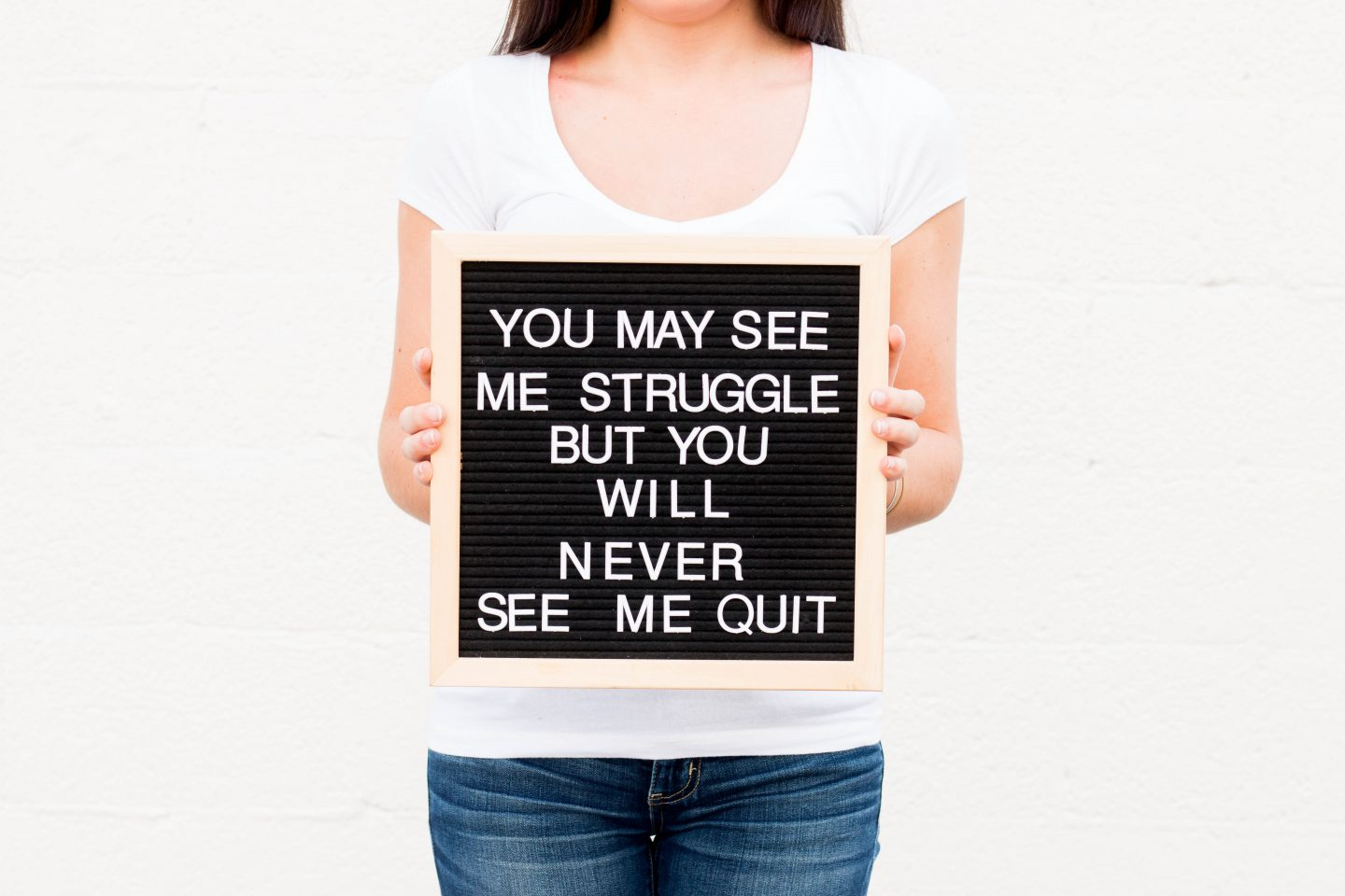 You may see me struggle but you will never see me quit. Quote. Woman holding quote plaque. Don't quit. Don't give up.